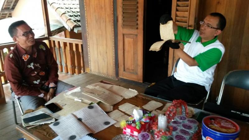 Zulkarnain sedang mengamati manuskrip kuno di Kabupaten Lampung Timur. (Foto: Dok. Zulkarnain/BLAJ)