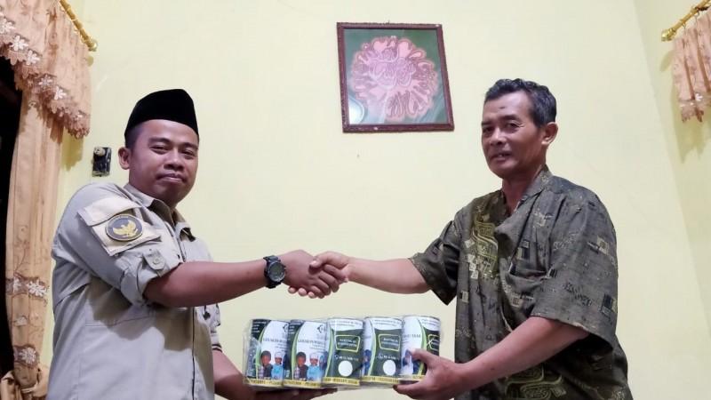 Penyerahan 300 kaleng kemandirian oleh Sekretaris LAZISNU Jombang, Nasrullah (kiri) ke pengurus MWCNU Mojoagung. (Foto: Istimewa)