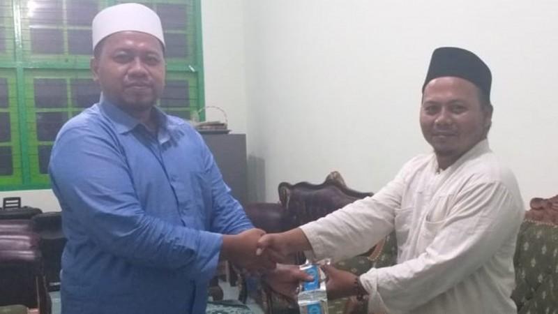 Pengasuh Pesantren Nurul Ulum, Desa Pace, Kecamatan Silo, Jember, Ustadz Tantowi (sebelah kanan) menyerahkan bantunan kopi Annajun kepada PCNU Jember yang diwakili oleh Gus Robith Qashidi. (Foto: NU Online/Aryudi AR)