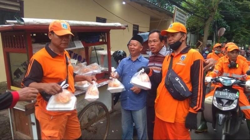 Di tengah wabah Covid-19, anggota Banser DKI Jakarta, Wasroni (berkemeja biru) membagikan lontong sayur salah satunya kepada petugas kebersihan, Jumat (27/3). Tindakan kecil bila dilakukan serentak akan berdampak besar.  (Foto ilustrasi: istimewa)