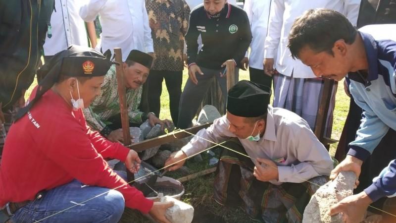 Ketua PCNU Jombang, KH Salmanudin Yazid meletakkan batu pertama pembangunan mushala SMKNU 01 Jombang. (Foto: Istimewa)