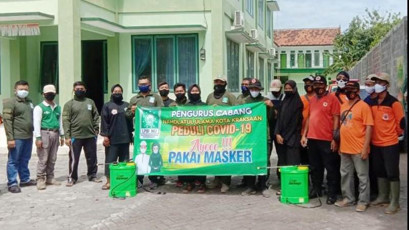 PCNU Kota Kraksaan Giat Semprotkan Disinfektan dan Bagikan Masker ke Warga