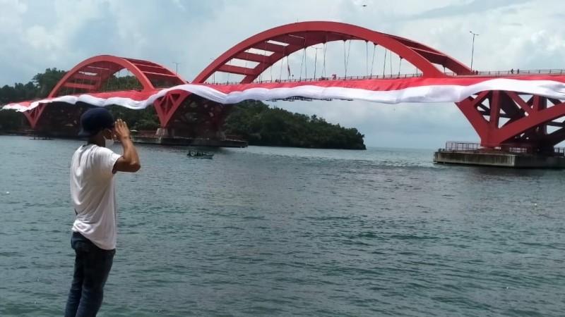 Bersinergi dengan Warga Papua, Banser Bentangkan Bendera di Jembatan Merah Youtefa